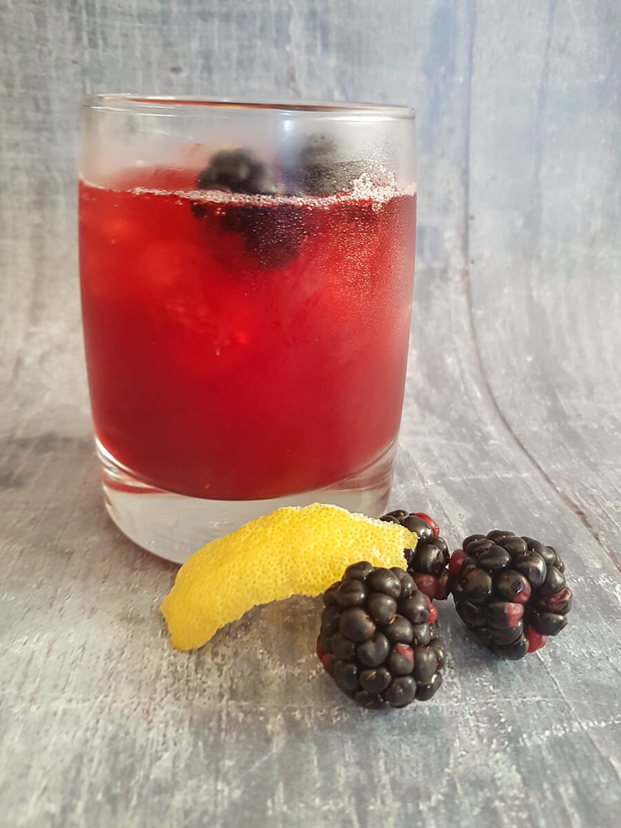 Blackberry gin sour cocktail - red cocktail in rocks tumbler with three blackerries and a slice of lemon to the side