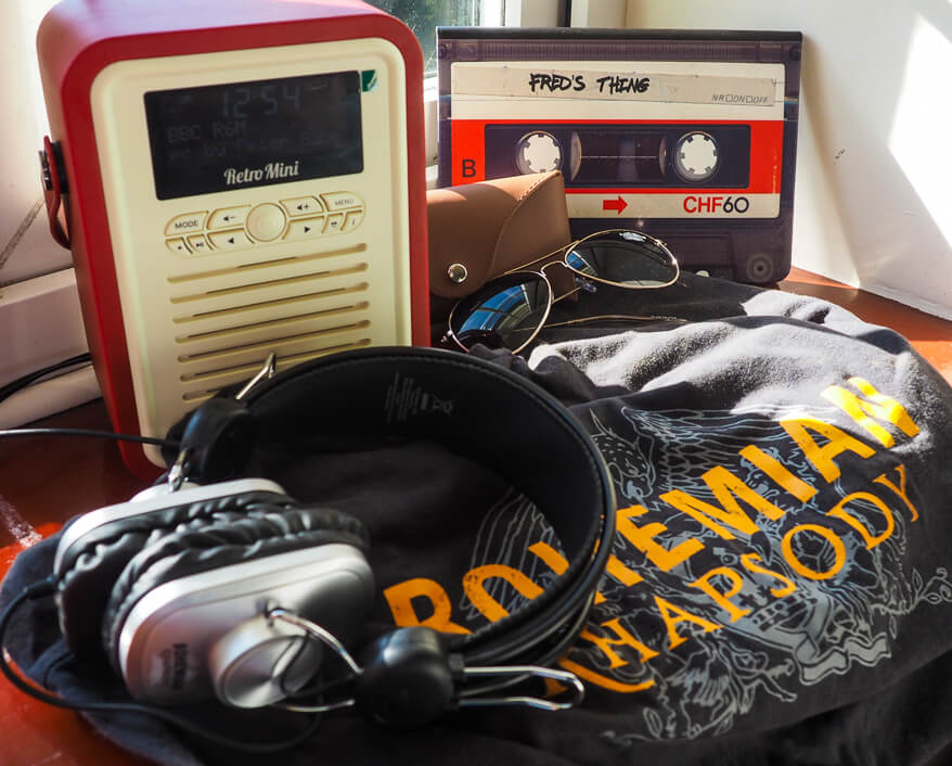 Liked & Loved - VQ Radio in red, Queen headphones, Queen Bohemian Rhapsody Tee shirt, Sunglasses, notebook